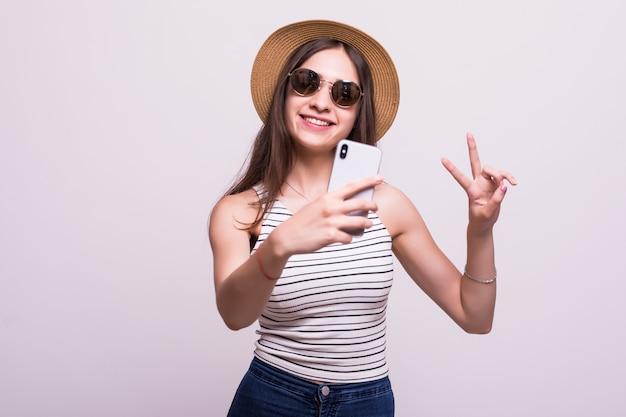 白い背景で隔離の携帯電話で自分の写真を撮るサングラス、帽子をかぶっているかなり若い女性