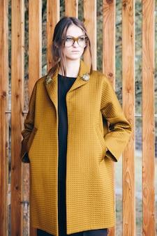 茶色の秋のファッションの服を着ているかなり若い女性