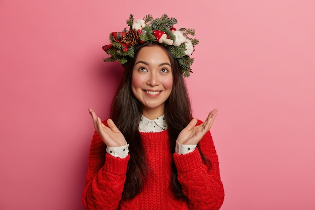 Pretty and young woman wearing christmas wreath on her head