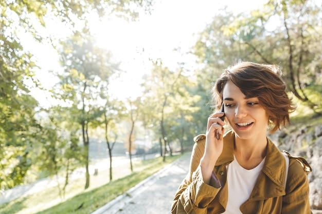 공원에서 산책하는 코트를 입고 예쁜 젊은 여자, 휴대 전화 통화