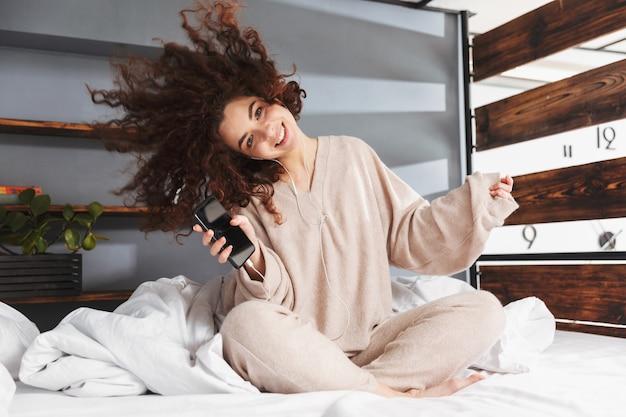 집에서 침대에 앉아 있는 동안 휴대폰으로 음악을 들으며 이어폰을 끼고 있는 예쁜 젊은 여성