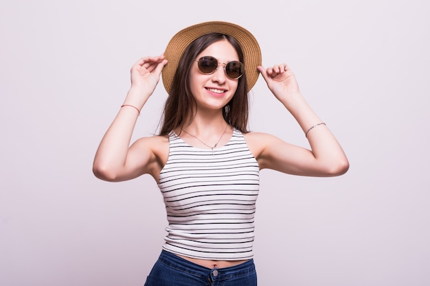 Pretty young woman wearing a hat, sunglasses isolated over white background