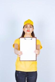 Bella giovane donna che indossa l'uniforme gialla del corriere che mostra la lavagna per appunti.