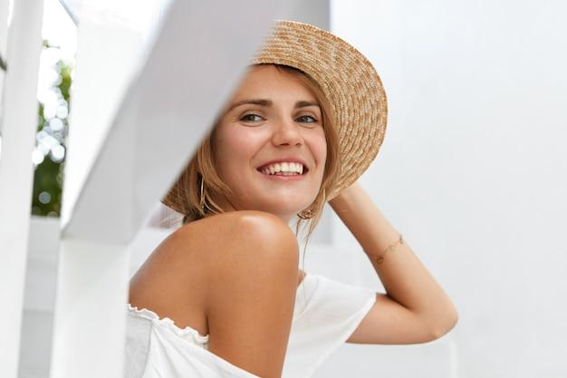 Piuttosto giovane donna indossa un cappello di paglia, mostra la sua spalla nuda, indossa una camicetta estiva alla moda con un ampio sorriso e un'espressione soddisfatta, felice di avere un giorno libero o un fine settimana