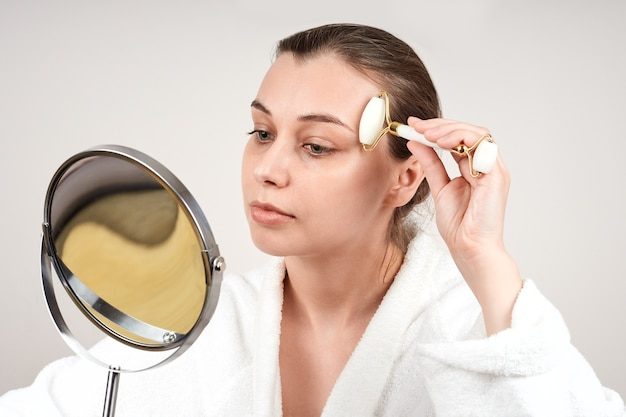 Pretty young woman in a white robe uses a jade roll to massage her face, looks in the mirror