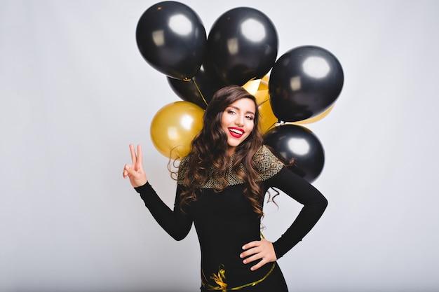 Piuttosto giovane donna su uno spazio bianco tenere palloncini oro e neri. incredibile ragazza con lunghi capelli ricci, in abito nero elegante