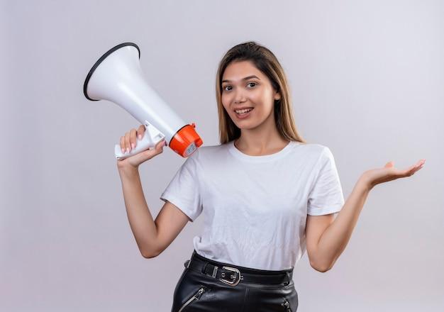 Una bella giovane donna in maglietta bianca che tiene il megafono su una parete bianca