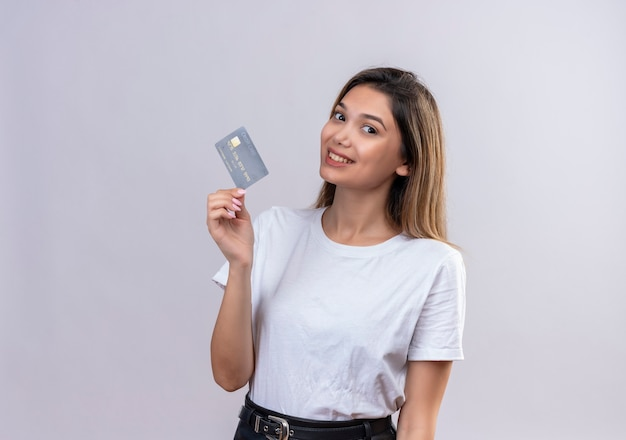 A pretty young woman in white t-shirt showing credit card on a white wall