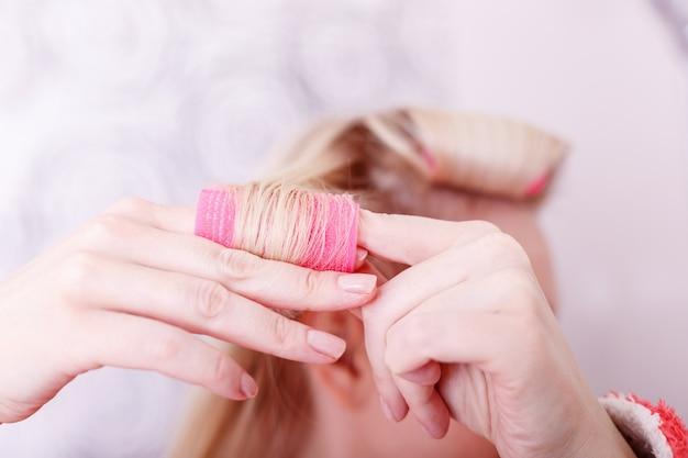 かなり若い女性がカーラーで髪を巻く