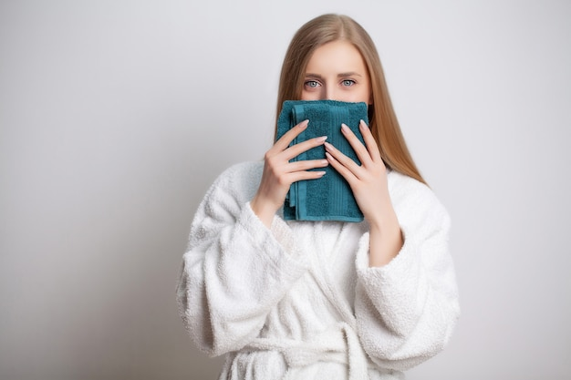 Pretty young woman wipes the face towel after taking a shower