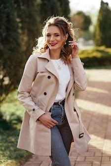 ベージュのトレンチ コートとジーンズが美しい日差しの公園でポーズをとるかなり若い女性
