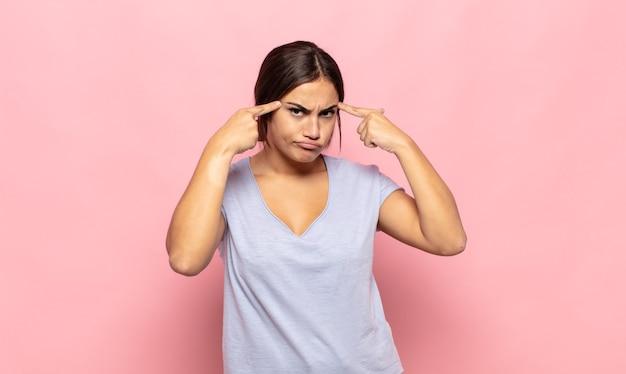 Довольно молодая женщина с серьезным и сосредоточенным взглядом, мозговой штурм и размышления над сложной проблемой