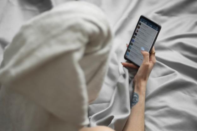 彼女の頭にタオルを持つかなり若い女性はベッドに横たわって携帯電話を保持し、ソーシャルネットワークをチェックします。リモートワーク、オンラインショッピング、