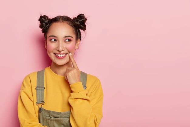 아시아 외모를 가진 예쁜 젊은 여성, 노란색 셔츠와 바지를 입고 두 개의 머리 만두가 있고 옆으로 보입니다.