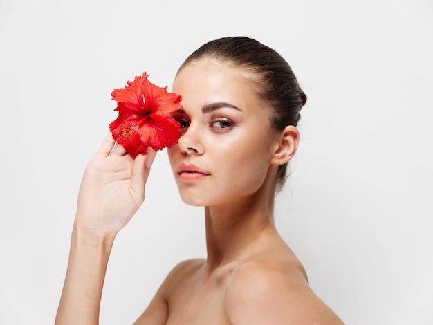 彼女の目の前に赤い花を持っている裸の肩を持つかなり若い女性。高品質の写真