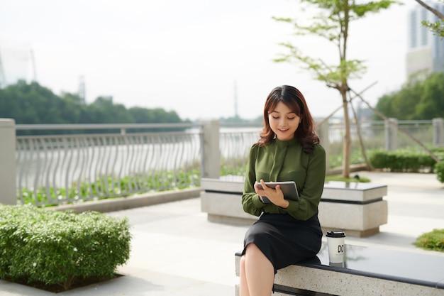 Довольно молодая женщина с красивой улыбкой с помощью планшета в парке