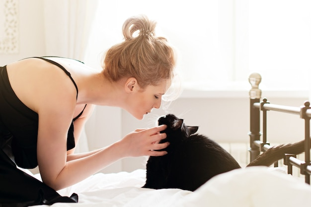 Pretty young woman with black cat in blanket in white bedroom