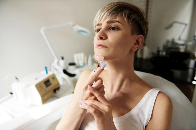 Довольно молодая женщина со светлыми короткими волосами делает лимфодренажный массаж шеи с помощью нефритового роликового массажера в косметологическом кабинете
