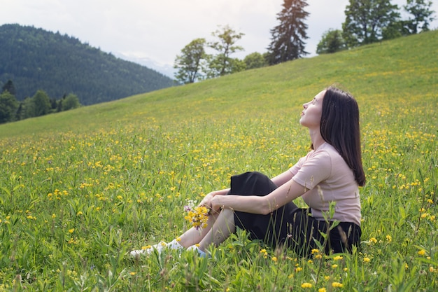 잔디밭에 앉아 야생화의 부케와 함께 예쁜 젊은 여자. 배경에 산입니다. 여름 화창한 날