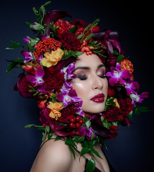 Pretty young woman with bright make-up with closed eyes surrounded with colorful wreath made of fresh flowers on the dark blue background