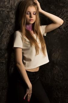 彼女の首に明るい化粧と紫のキラキラを持つかなり若い女性