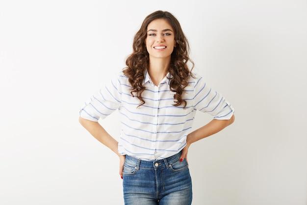 Довольно молодая женщина с откровенной улыбкой, хипстерском стиле, одетая в джинсы, рубашку, изолированную на белом фоне, вьющиеся волосы