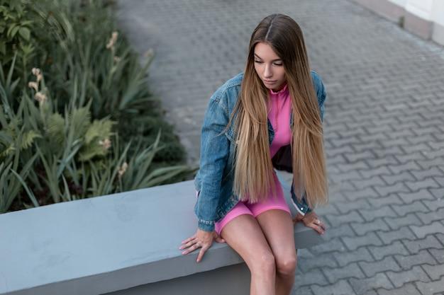 거리에서 쉬고 트렌디 한 블루 데님 재킷에 여름 스포티 한 매력적인 정장에 세련 된 긴 금발 머리를 가진 예쁜 젊은 여자. 현대 유럽 소녀 모델은 도시에서 이완합니다. 여름 스타일.