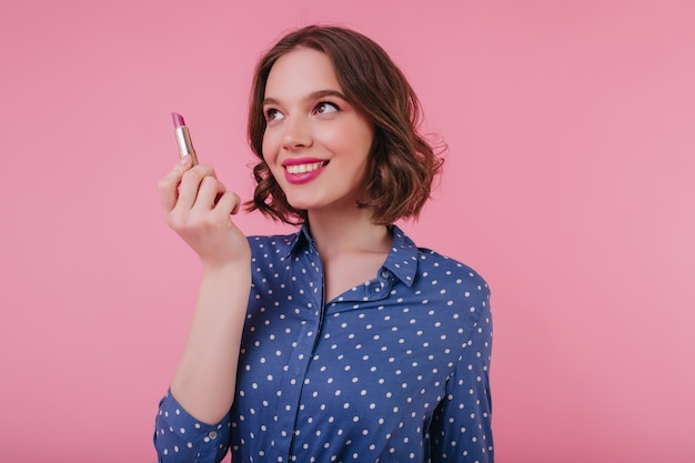Pretty young woman with curly hair isolated on pink wall with lipstick in hand. smiling lovable girl wears blue blouse.