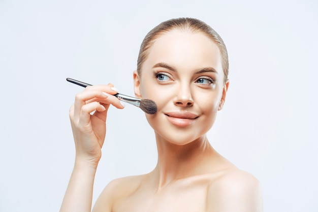Pretty young woman with dark combed hair, applies powder foundation on face with beauty brush