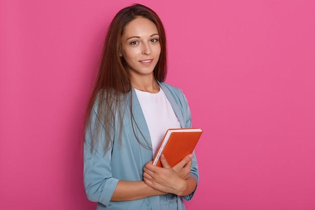 Милая молодая женщина с темными прямыми волосами стоя с записной книжкой вдыхает