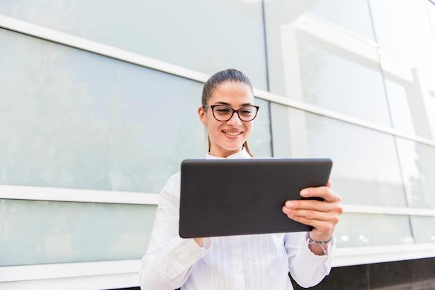Милая молодая женщина с цифровой таблеткой офисным зданием