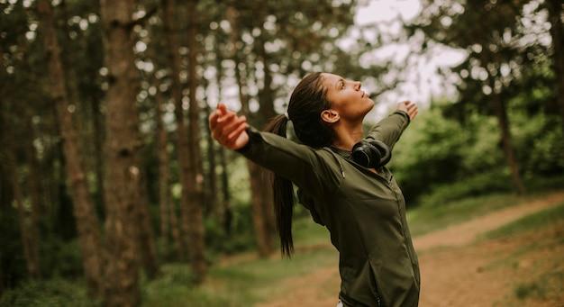 外でのトレーニングを楽しんでいるので、森の中で腕を前に出すイヤホンを持ったかなり若い女性