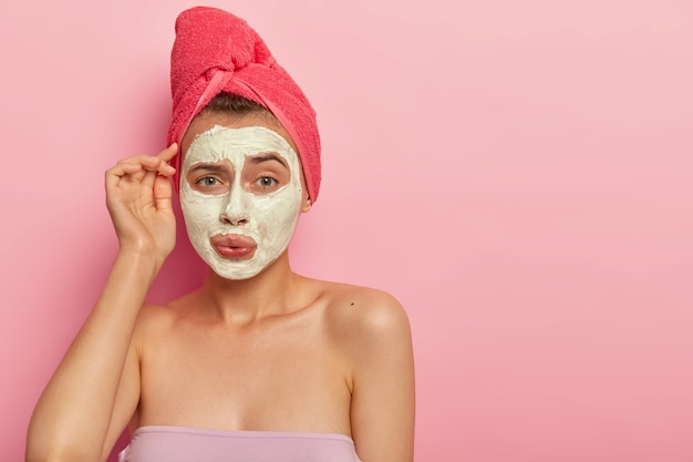 Pretty young woman with embarrassed expression, applies cream mask on face for reducing skin problems, has discontent look, takes bath every day, enjoys hygienic procedures. health care