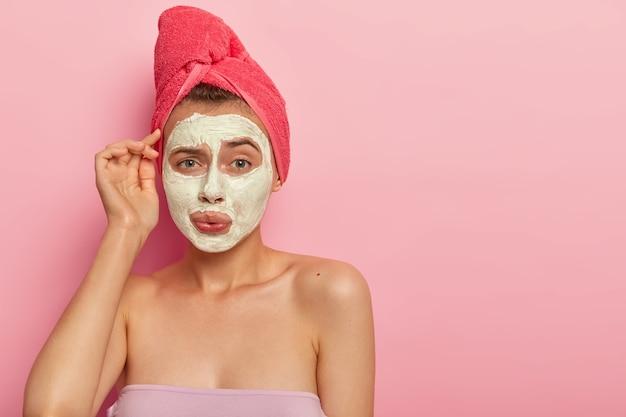 Bella giovane donna con un'espressione imbarazzata, applica una maschera in crema sul viso per ridurre i problemi della pelle, ha un aspetto scontento, fa il bagno ogni giorno, gode di procedure igieniche. assistenza sanitaria