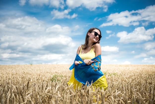 小麦畑の夏の時間にウクライナの旗を持つかなり若い女性