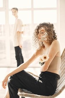 花を持つかなり若い女性がフォトセッションを持っています。椅子に座っている巻き毛の少女。後ろにいる男。