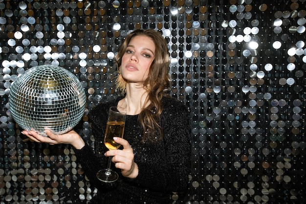 Pretty young woman with flute of champagne and disco ball looking at you while toasting at party in the night club