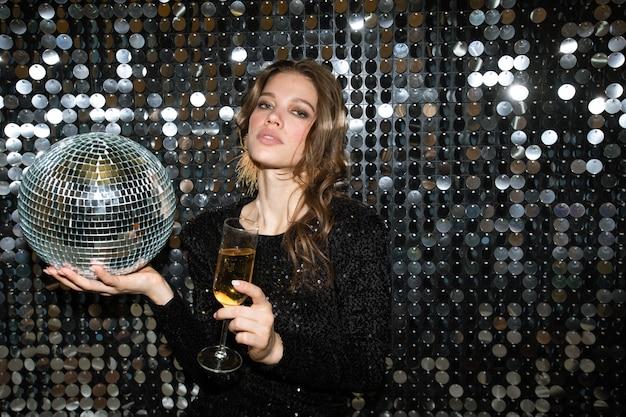 Довольно молодая женщина с бокалом шампанского и дискотечным шаром смотрит на вас во время тоста на вечеринке в ночном клубе