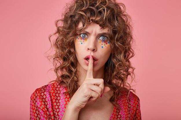 우울한 표정으로 예쁜 젊은 여성이 찡그린 얼굴을하고 입술에 앞쪽 손가락을 유지하고 소음을 일으키지 말고 진정하도록 촉구합니다.