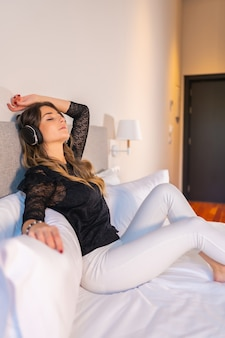 Довольно молодая женщина с наушниками, слушающая музыку, расслабилась в своей домашней постели с закрытыми глазами