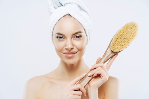Pretty young woman with healthy skin, takes care of personal hygiene, holds bath brush, wrapped towel on head, stands shirtless indoor, white wall. women, skin care, freshness concept.