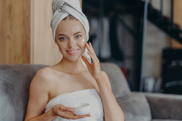 Pretty young woman with healthy smooth skin applies face cream, wears wrapped towel on head after taking shower, poses on comfortable sofa.