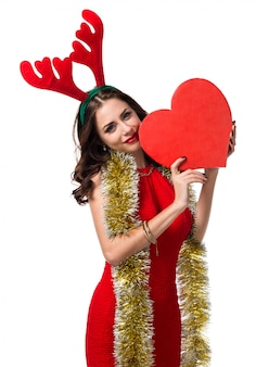 Pretty young woman with heart and reindeer antlers. Christmas concept
