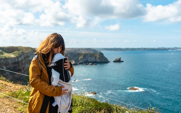 A pretty young woman with her baby on the coastal path next to the fort des capucins a rocky, clifftop islet in the town of roscanvel on the crozon peninsula in france.