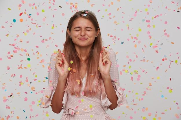 Красивая молодая женщина с длинными волосами и открытым ртом в розовом платье празднует день рождения с конфетти