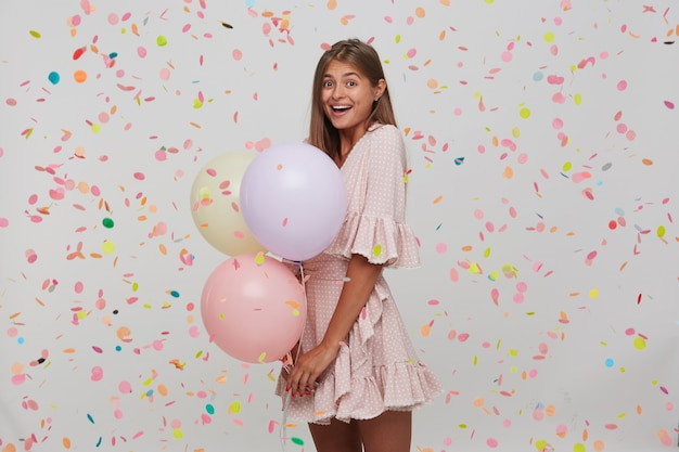 Pretty young woman with long hair and opened mouth wears pink dress is celebrating birthday with confetti