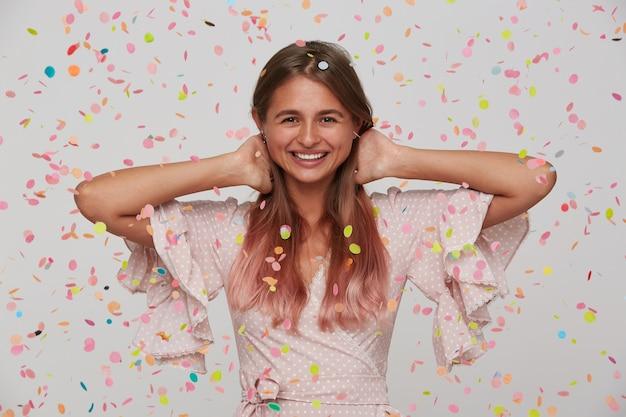 Bella giovane donna con i capelli lunghi e la bocca aperta indossa un abito rosa festeggia il compleanno con i coriandoli