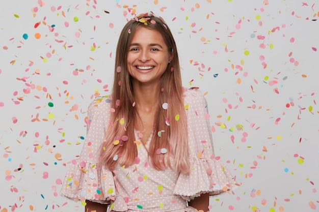 Bella giovane donna con i capelli lunghi e la bocca aperta indossa un abito rosa con coriandoli