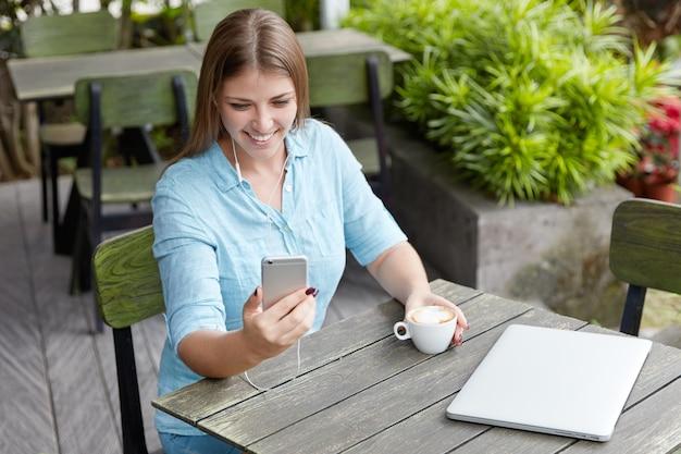 Довольно молодая женщина с длинными волосами, сидя в кафе с телефоном