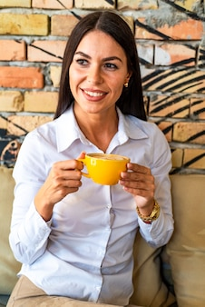 Pretty young woman with mug in hands drinking coffee in the morning at restaurant